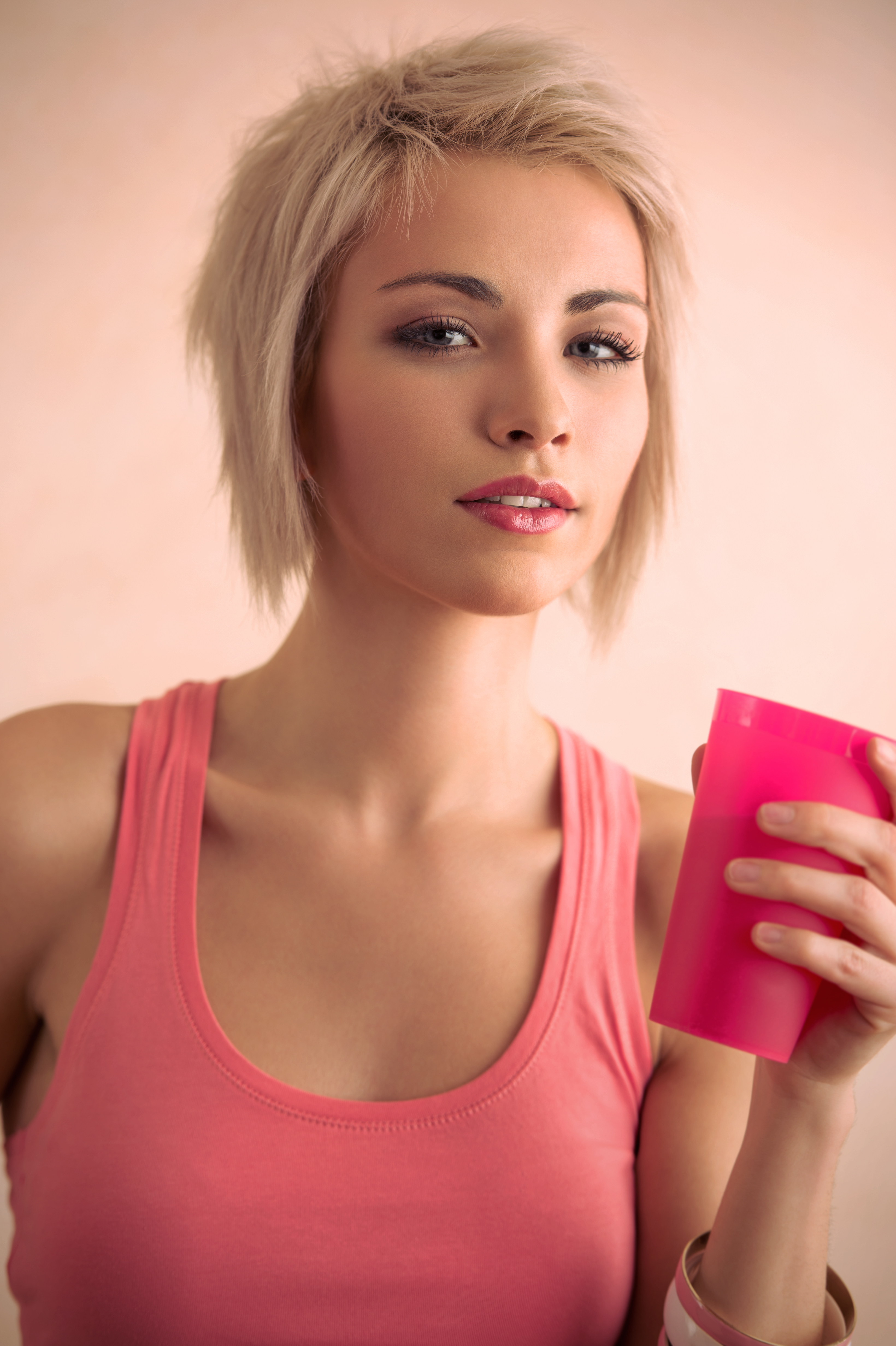 Hot blond girl with short hair holding plastic cup and looking at camera